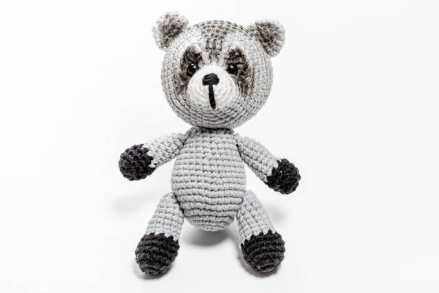 Crochet handmade raccoon toy on a white background