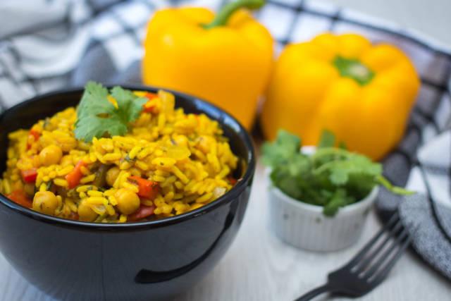 Curryreis in schwarzer Schüssel garniert mit Petersilie