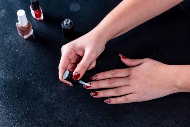 Frau lackiert ihre Fingernägel mit rotem Nagellack und festlichen Zeichnungen auf dunklem Tisch