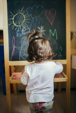 Little girl learning to draw and write on the black board