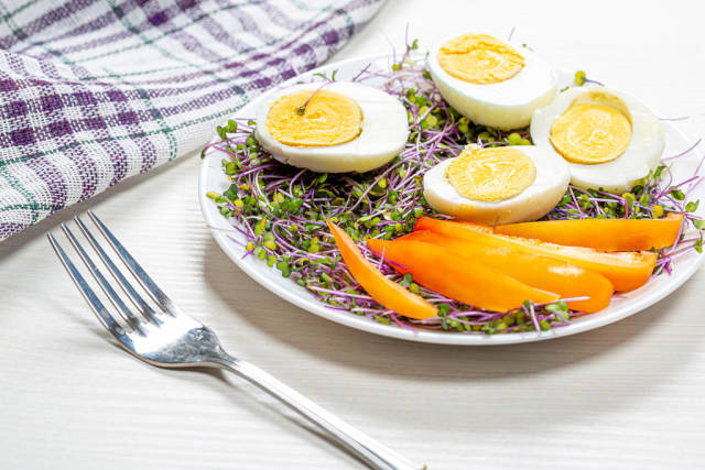 Halves of boiled eggs with micro greens and pieces of bell pepper in a white plate