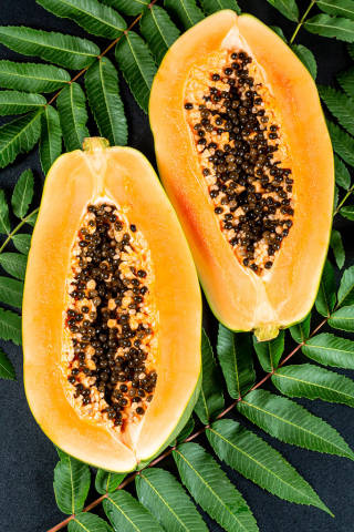 Ripe papaya halveson a black background with leaves, top view