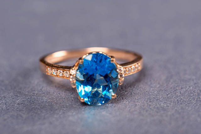Gold ring with blue topaz on a purple background