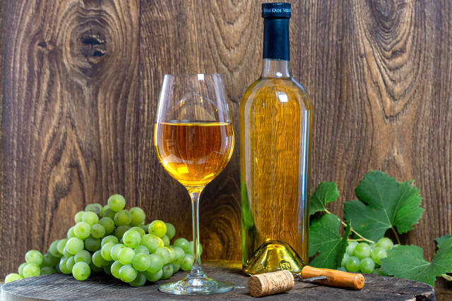 White wine with fresh grapes and corkscrew on brown wooden background
