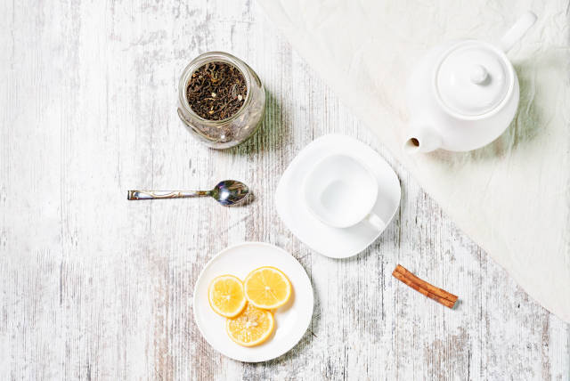A bowl of dry tea, lemon slices and a pot of hot water for making healthy tea
