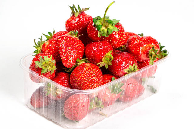 Plastic box with fresh strawberries on white