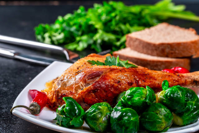 Baked chicken leg with Brussels sprouts on a plate with black bread and parsley