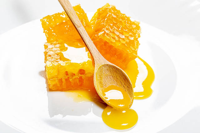 Honeycomb with wooden honey spoon and honey