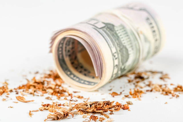 Twisted dollar bills and tobacco on a white background