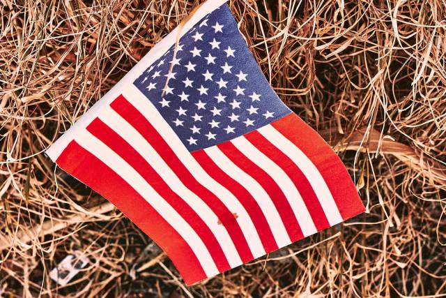 Eine US-Amerikanische Flagge mit einem Blutfleck liegt im Stroh. US-Politik im Chaos