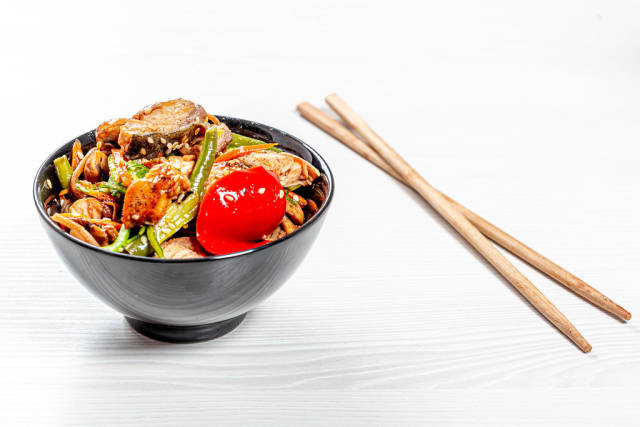Soba noodles with tuna, asparagus, pepper and mushrooms in sweet and sour sauce in black bowl with chopsticks on white wooden background