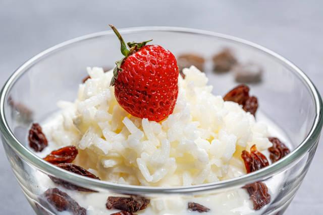 Milk porridge with rice, raisins and strawberries. Close up