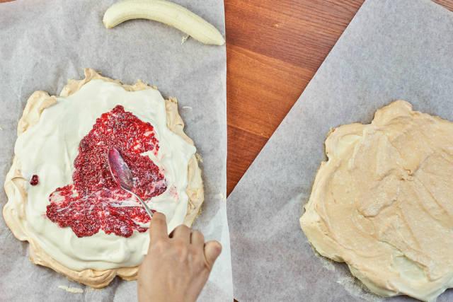 Woman smearing raspberry jam on the sweet cake
