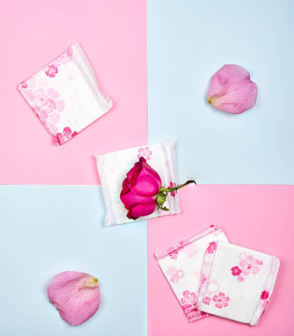 Sanitary pads and flowers on color background