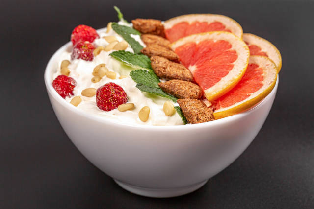Oatmeal with pine nuts and grapefruit pieces in a bowl on a black background