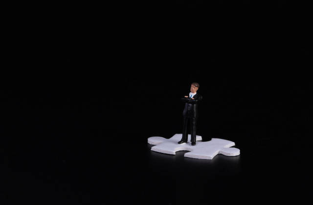 Businessman standing on puzzle piece wtih black background