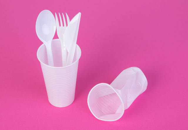 Single use plastic objects on pink background