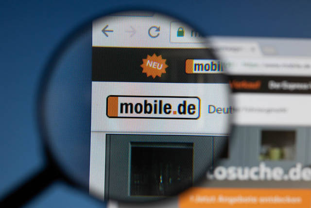 Mobile.de logo on a computer screen with a magnifying glass