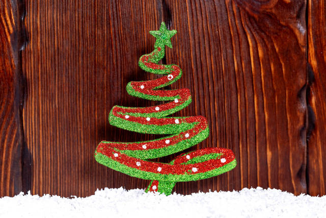 Colorful Christmas toy tree on the background of wooden boards and snow