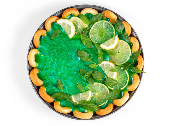 Top view, pie with green mirror glaze and citrus slices