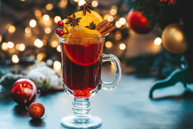 Glass of mulled wine on a beautiful Christmas background with Christmas tree and bokeh