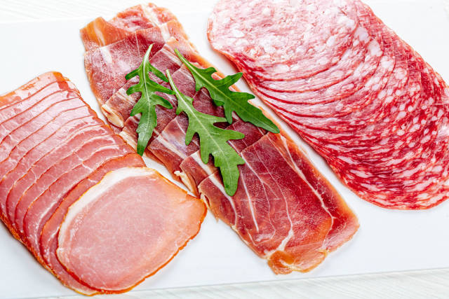 Ham, jamon and salami with fresh arugula leaves