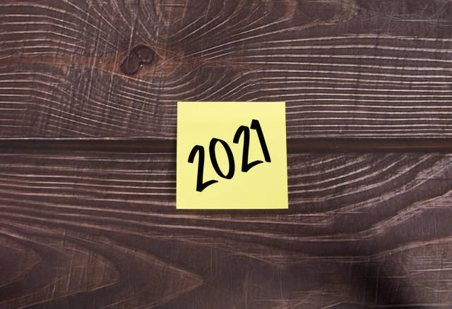 Yellow sticky note with 2021 text on wooden table