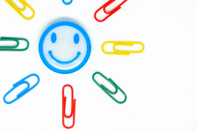 Close up shot of smiley magnet with paperclips