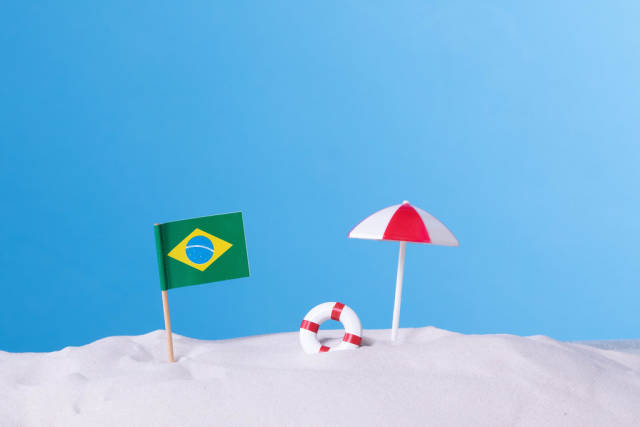 Flag of Brazil with beach umbrella on blue background