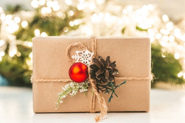 Christmas gift on a blurred background of a glowing garland and branches of a Christmas tree
