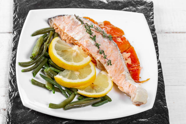 Baked salmon garnished with asparagus and carrot with herbs
