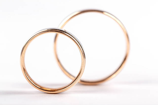 Two gold wedding rings on white