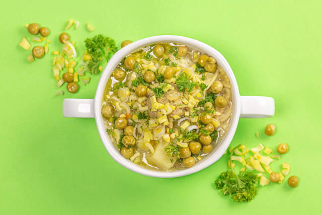 Top view, soup with meatballs, peas and herbs on a green background