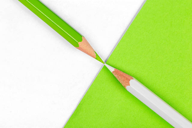 Green pencil on white and white pencil on green background