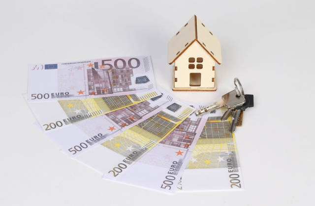 Tiny wooden house with keys and Euro banknotes on white background