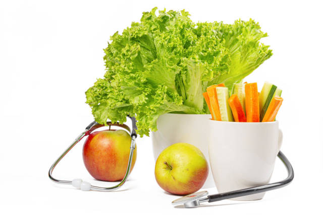 Medical stethoscope with fresh vegetables and apples