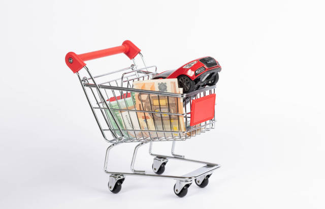 Red car with Euro banknotes in shopping cart