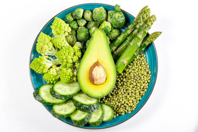 Top view, romanesco cabbage, cucumber, avocado, Brussels sprouts, asparagus and green peas on a white background