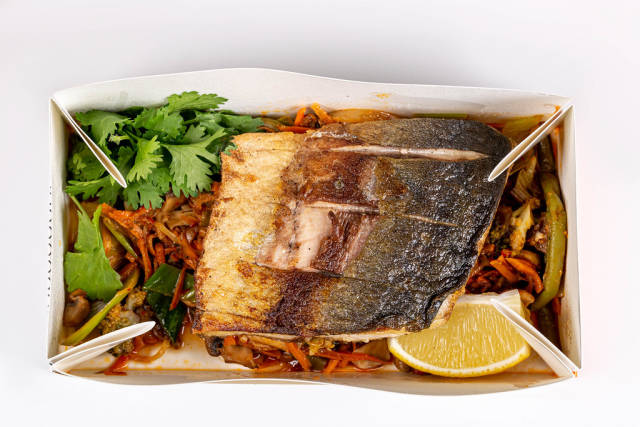 Tuna steaks with vegetable garnish in a cardboard box