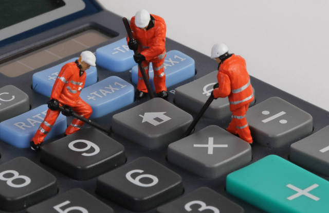 Miniature workers repairing home button on calculator