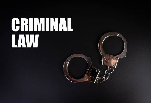 Metal handcuffs on black background with Criminal Law text