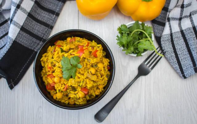 Draufsicht von Curryreis in schwarzer Schüssel garniert mit Petersilie