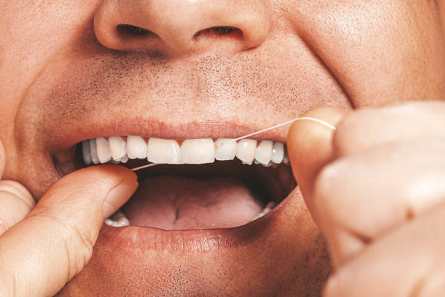 Adult man cleaning flossing his white teeth with dental floss