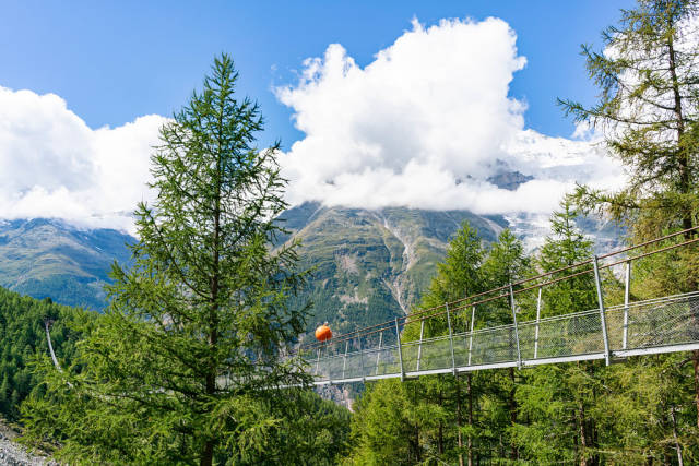 First section of Charles Kuonen suspension bridge with mountain glacier in the background