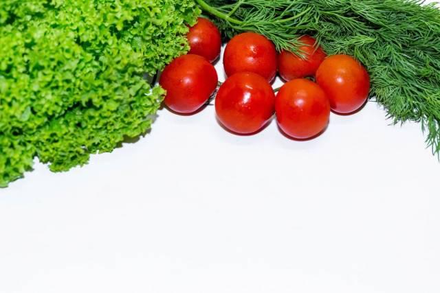 Leuchtend rote Tomaten vor Kraussalat und einem Strauch Dill auf weißem Hintergrund