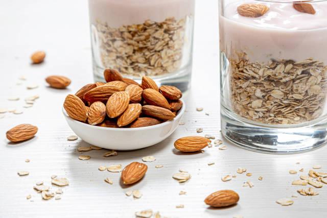 Bowl full of almonds and oatmeal porridge behind