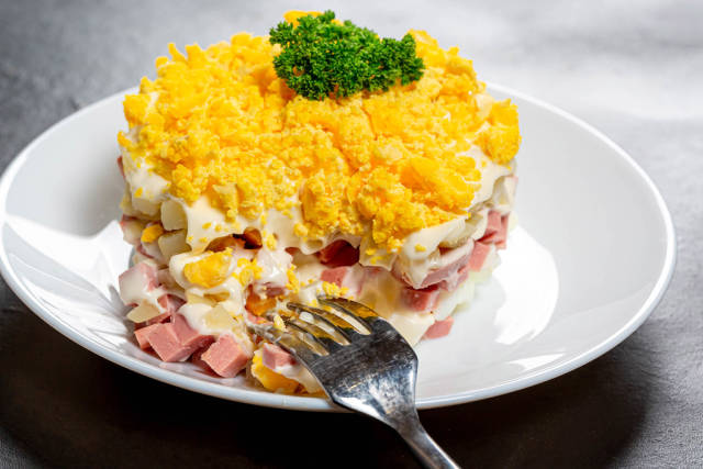 Close-up salad with boiled potatoes, eggs, ham and sauce on a white plate with a fork