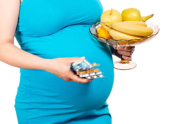 Young womans holding blister packs of pills and fresh fruits. Concept receiving vitamins in pregnancy time