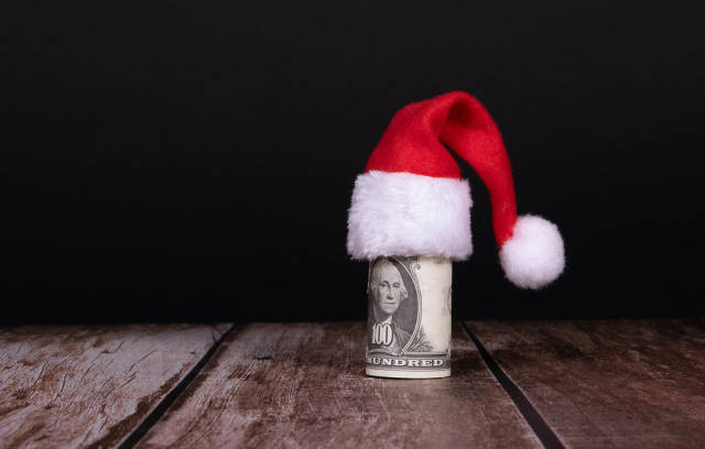 Money roll with Christmas hat on black background