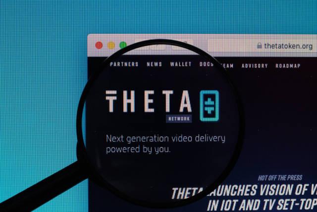 Theta Token Logo auf der Internetseite, vergrößert dargestellt unter einer Lupe
